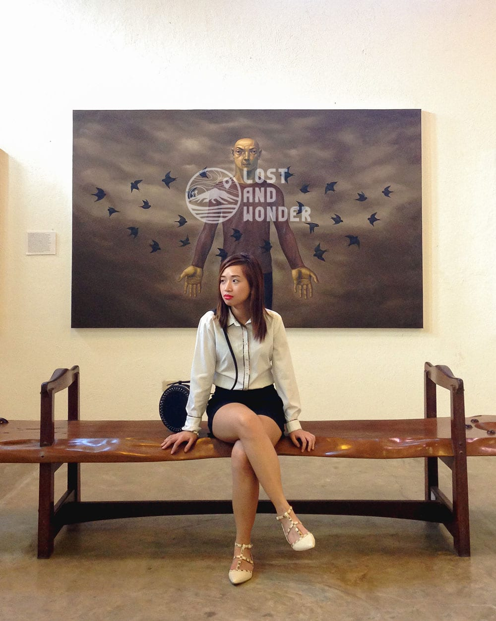 Photo of a lady posing besides and artwork