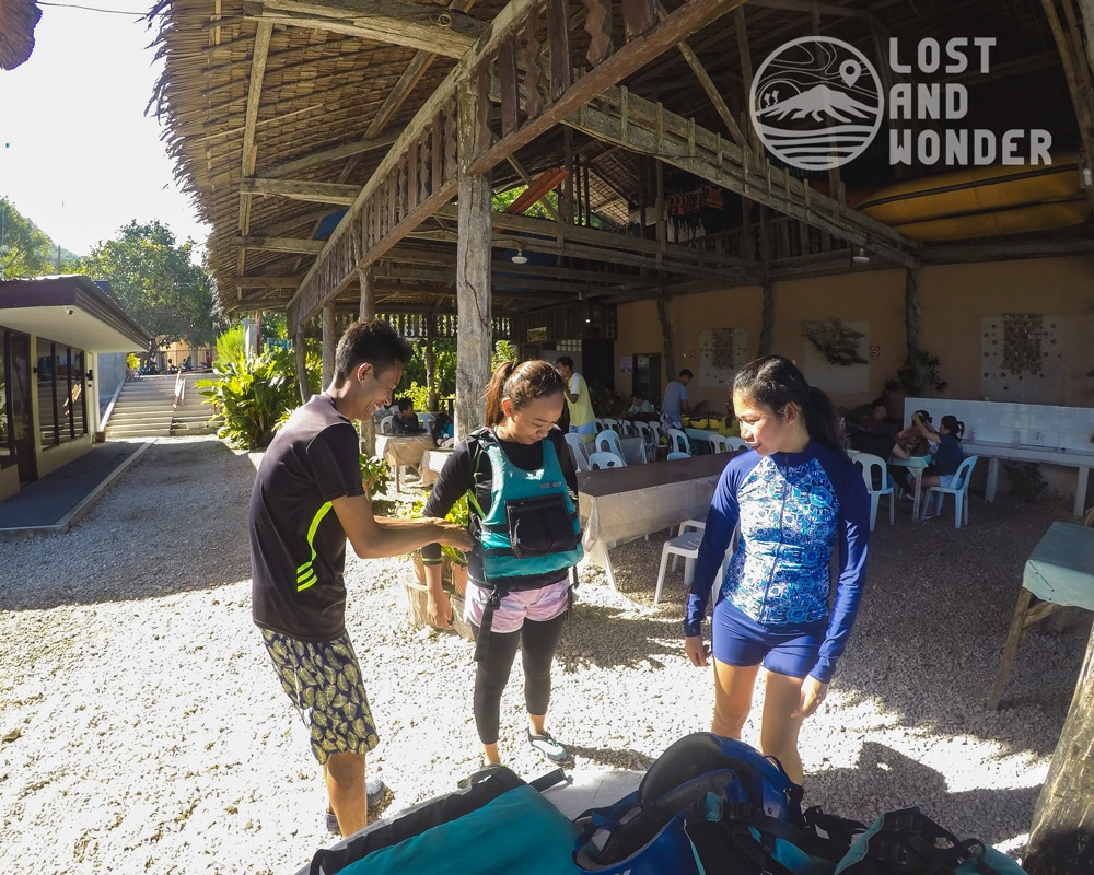 Photo of our tour guide helping travelers wear life gears in Kawasan Canyoneering